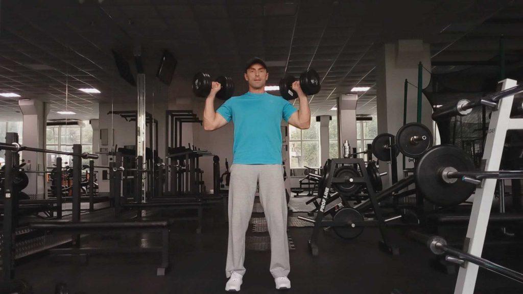 Упражнения с гантелями для дельтовидных мышц. Жим гантелей стоя